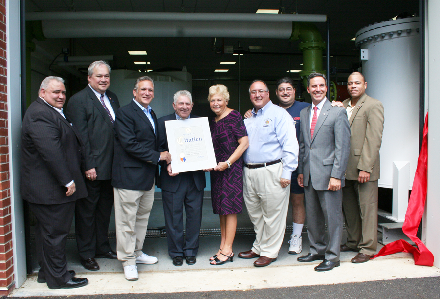 (L-R) Hicksville Water District Board of Commissioners Chairman Karl Schweitzer, Town of Oyster Bay Receiver of Taxes James Stefanich, Hicksville Water District Board of Commissioners Chairman Nicholas Brigandi, Nassau County Executive Edward Mangano, Assemblyman Michael Montesano, Legislator Rose Walker, Hicksville Community Council Vice President Stan Kobin, Senator Jack Martins and Hicksville Chamber of Commerce President Lionel J. Chitty come together at Hicksville Water District's Plant #6 as the County Executive presents a citation to the Hicksville Water District in recognition of their contributions to the Hicksville community.